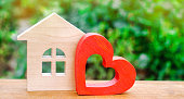 """House with a red wooden heart. House of lovers. Affordable housing for young families. Valentine's day house. """"Home Sweet Home"""". life insurance"""