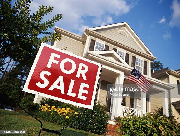 House with American flag and 'for sale' sign, low angle view
