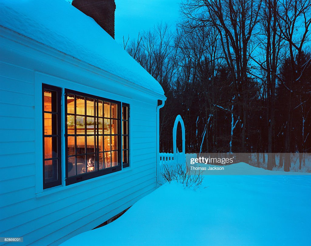 house with fireplace in snowy landscape stock photo getty images