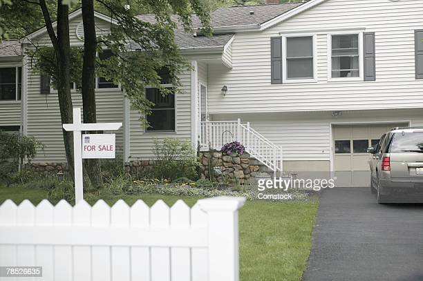 House with for sale sign in front yard
