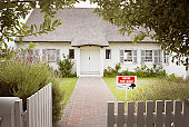 House with for sale sign in yard and open wooden fence