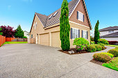Clapboard siding house with two car garage and driveway. Viw of green beautitul landscape