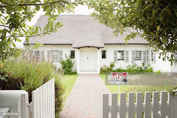 House with wooden fence and sold sign
