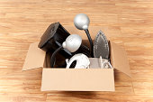"""Cardboard box filled with an assortment of old electric household appliances, ready for moving or a garage sale. Items in the box include a coffee maker, mixer, iron, small heater, and lamps.Please a"