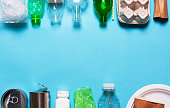 Household waste on a blue background. The concept of sorting plastic, polyethylene cardboard, paper, glass. Environment protection