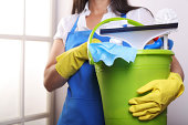 Woman in blue apron holding a green plastic bucket with cleaning tools(Shallow Depth of Field)Other relates images: