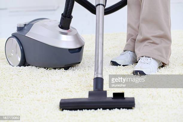 Housemaid's legs and vacuum on a white carpet.