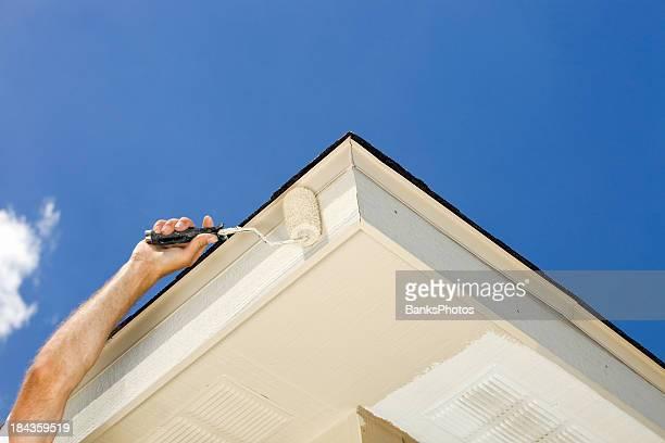 Housepainter Rolling Paint on Roof Fascia