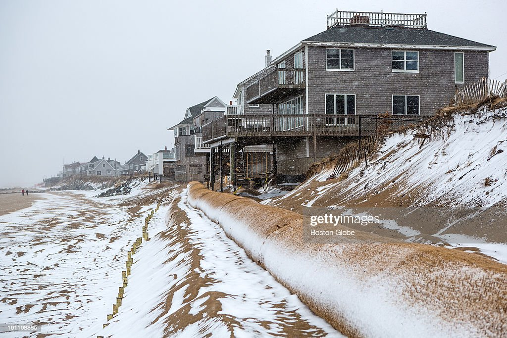 Houses along the beach on Plum Island are guarded by a barrier of sand as a large winter storm approaches.