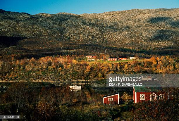 Houses and boat in a fjord in autumn along County road 17 Helgeland Nordland county Norway