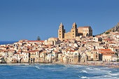 Houses along the shoreline and cathedral in background Cefalu Sicily.