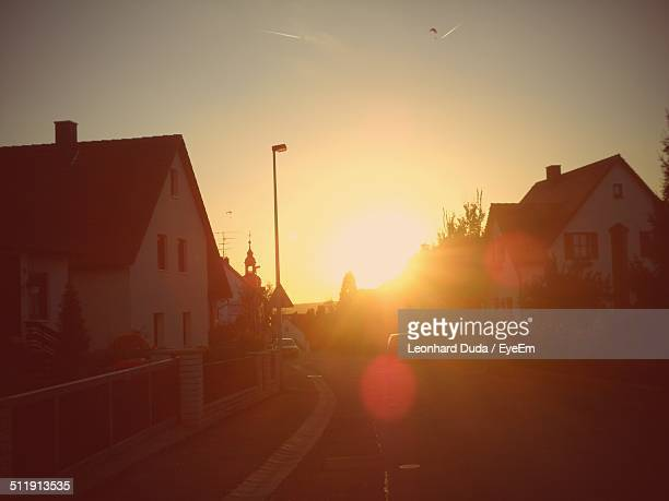 Houses and street against clear sky at sunset