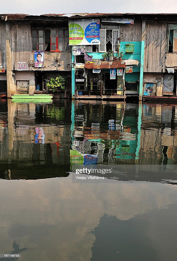 Houses are reflected on the placid floodwater of Artex Compound in Malabon City on April 28, 2013 in Manila, Philippines. The residents of the former textile compound had to adjust their daily lives after flood waters submerged their low-lying village in 2004.