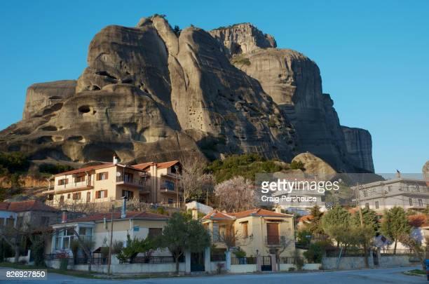 Houses below huge rock mountain of Meteora.