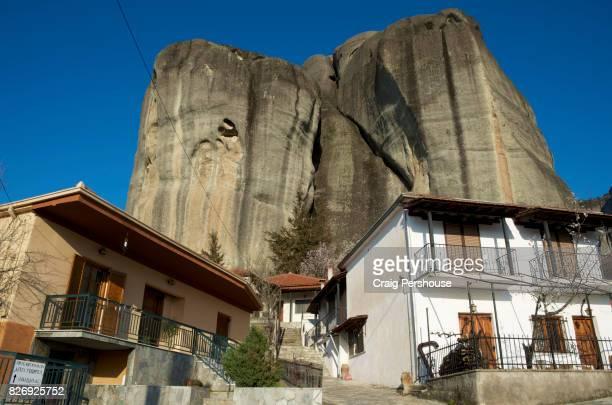 Houses below huge rock mountain.