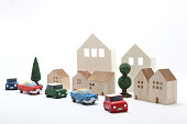 Houses, cars, and trees on white background. Cityscape of toys.
