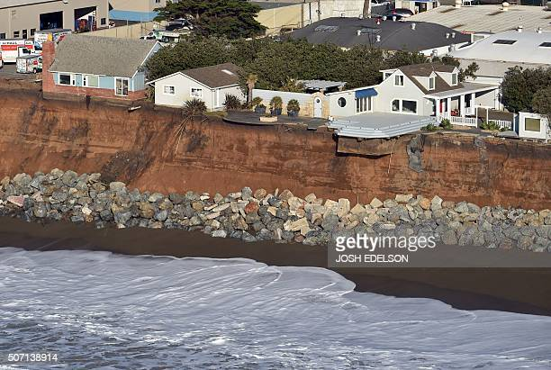 Houses hang on the edge of an eroding cliff in Pacifica California on January 27 2016 Storms and powerful waves caused by El Nino have been...