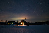 Houses in the Russian village. Winter, frosty night. Starry sky over the roofs of houses.