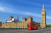 double-deck red bus on Westminster Bridge with Big Ben and Houses of Parliament on the background in London, UK