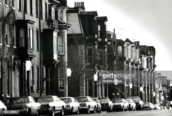 Houses on West Broadway in South Boston seems stacked on top of one another with cars on street