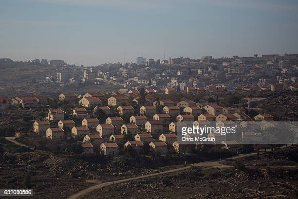 Houses part of an Israeli settlement are seen in front of an Arab town on January 16 2017 in Amona West Bank 70 countries attended the recent Paris...