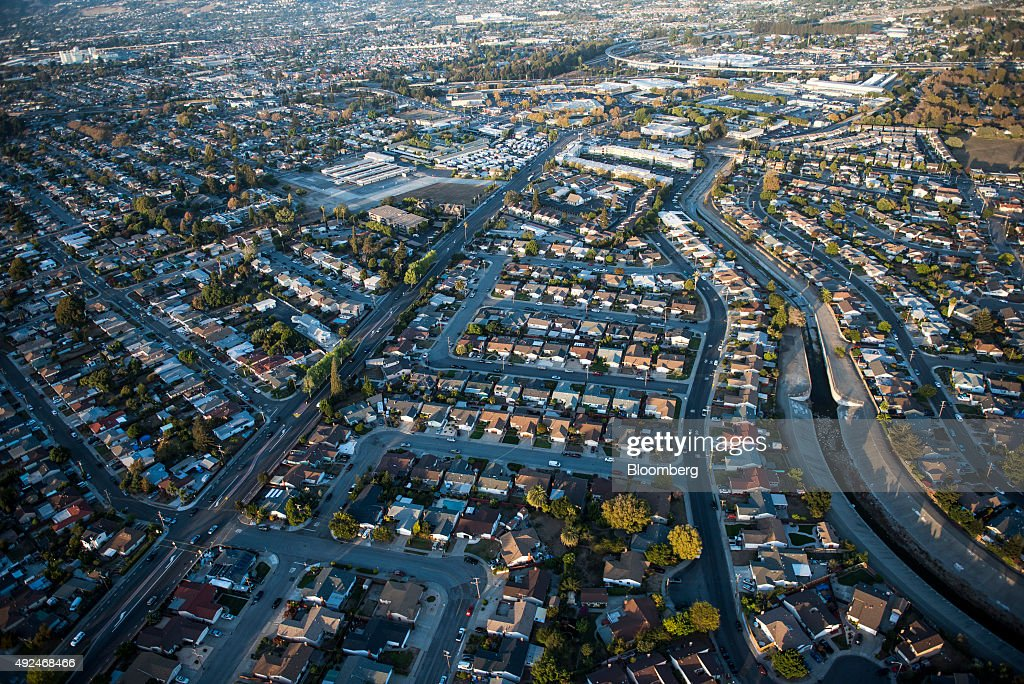 Houses stand in this aerial photograph taken above Alameda, California, U.S., on Monday, Oct. 5, 2015. With tech workers flooding San Francisco, one-bedroom apartment rents have climbed to $3,500 a month, more than in any other U.S. city. Photographer: David Paul Morris/Bloomberg via Getty Images