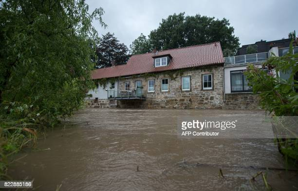 Houses stand next to the high level river Innerste on July 26 2017 in Hildesheim northern Germany Ongoing rain led to high level of the river in...