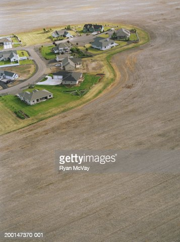 Houses surrounded by harvested farmland, aerial view : Stock Photo