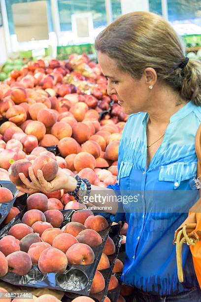 Housewife buying peaches