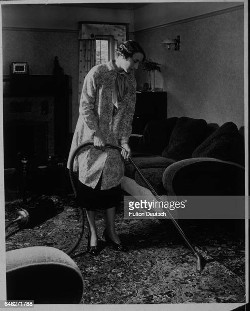 A housewife cleaning a sitting room with an electrical vacuum cleaner