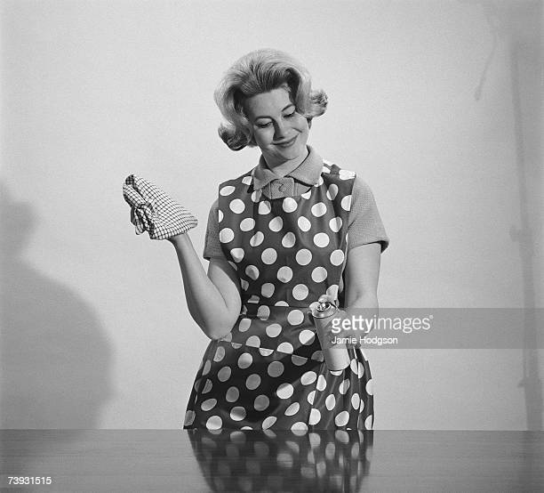 A housewife cleans a wooden surface using Cooper's spray 16th April 1962