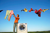 Housewife Hanging Laundry on a Washing Line Standing by a Washing Machine
