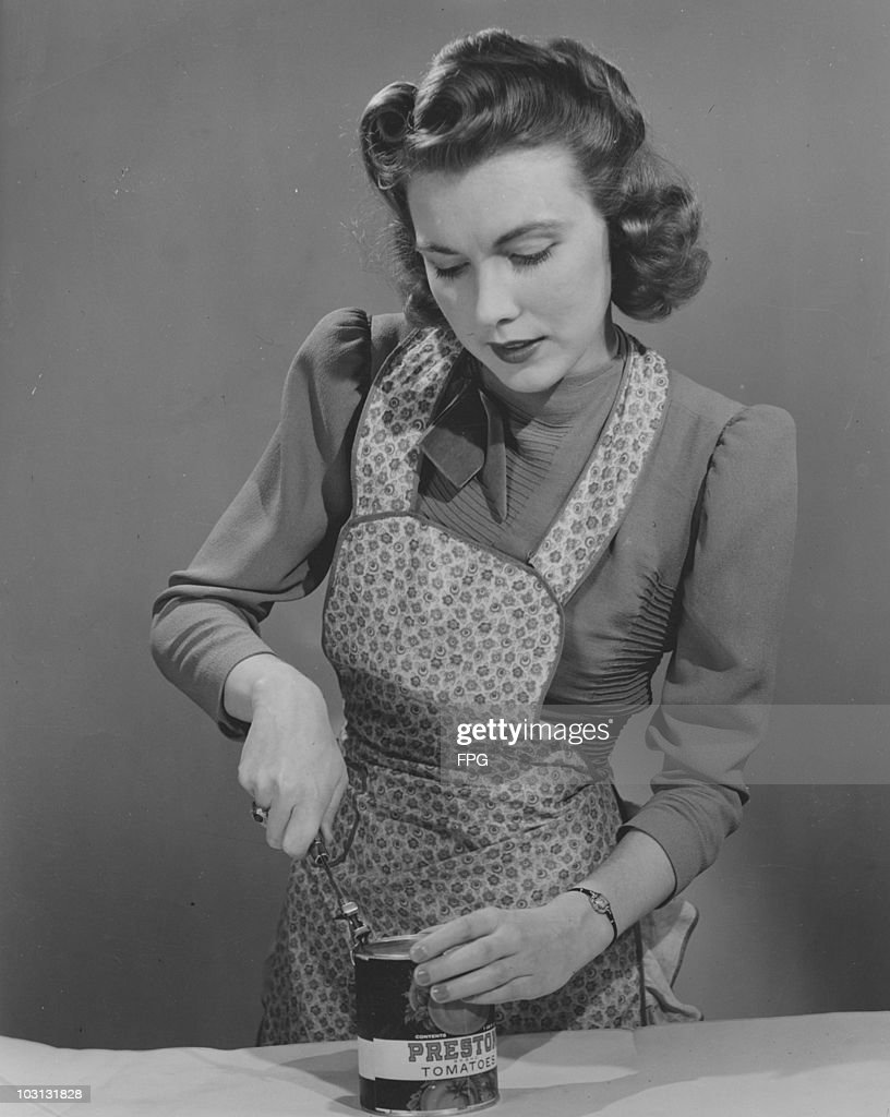 A housewife opening a tin of tomatoes circa 1945