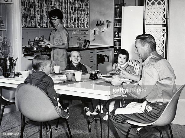 A housewife prepares breakfast for her husband and three young children in their kitchen