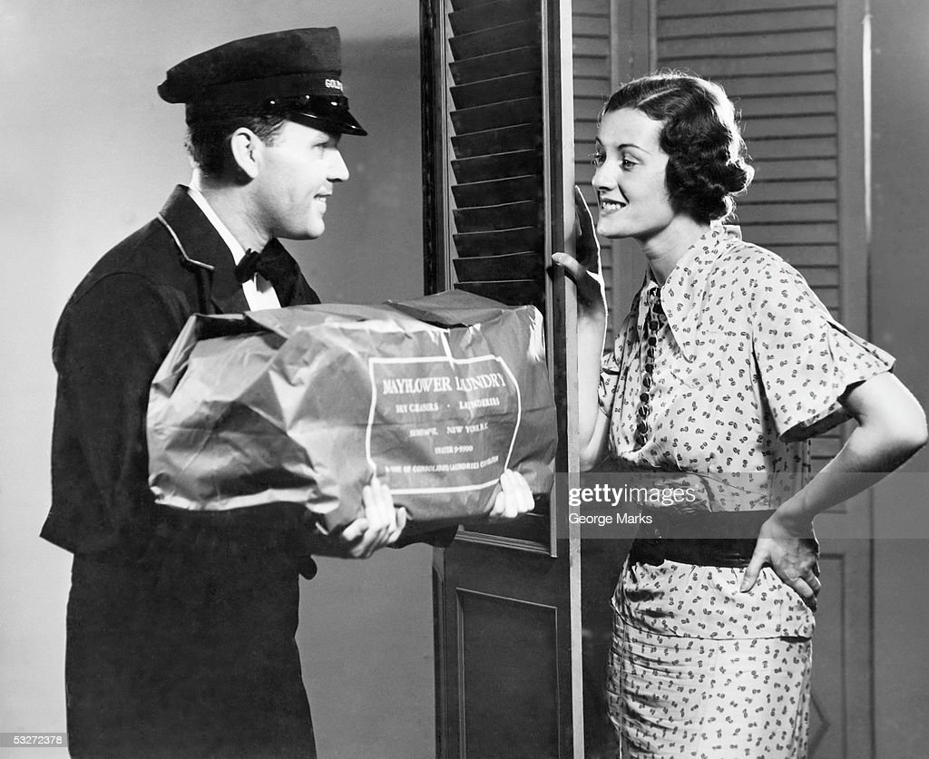 Housewife receives laundry delivery : Stock Photo