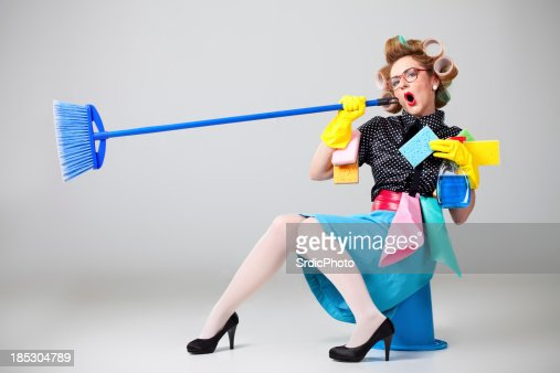 Housewife sitting on bucket and singing into broom