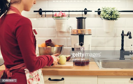 Housewife slicing fruits in the kitchen : Stock Photo