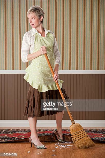 Housewife Sweeping Dirt Under The Rug