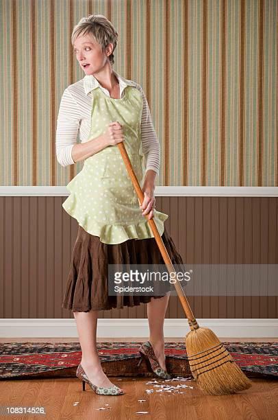 Hausfrau atemberaubenden Schmutz unter den Teppich
