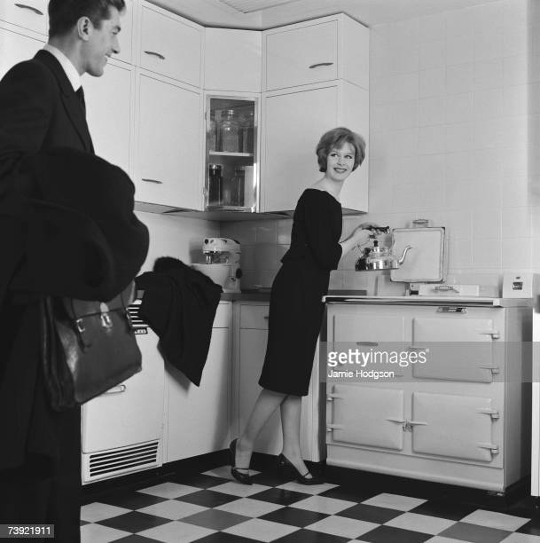 A housewife uses her Rayburn aga to boil the kettle as her husband returns home from work circa 1960 A photoshoot for Rayburn