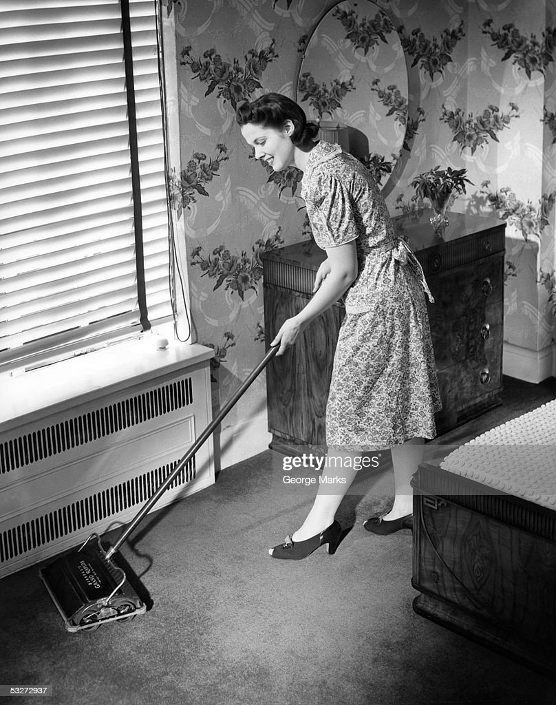 Housewife using carpet sweeper in home : Stock Photo