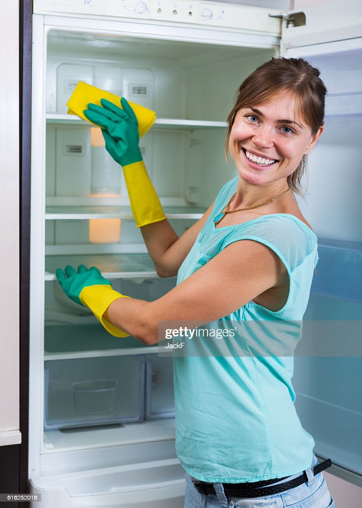 Housewife washing fridge with detergent : Stock Photo