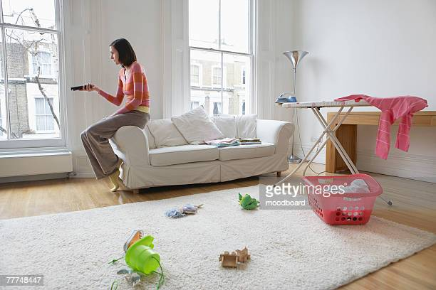 Housewife Watching Television in Messy Living Room