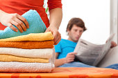 Housewife working while her husband reading newspaper