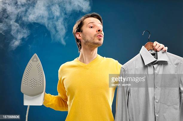 Houseworks, man holding iron in one hand, shirt in other