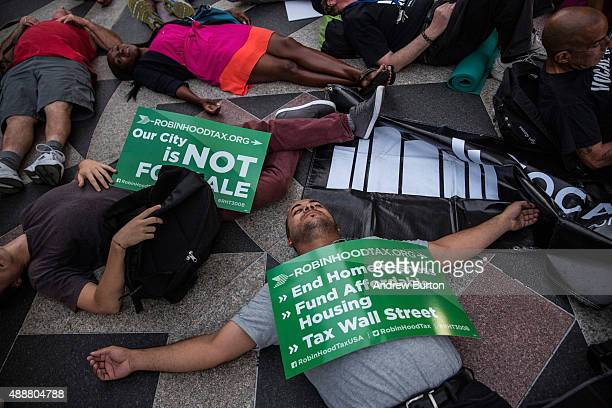 Housing activists host a 'die in' at New York Police Department headquarters during a march from Zuccotti Park to New York City's City Hall to demand...