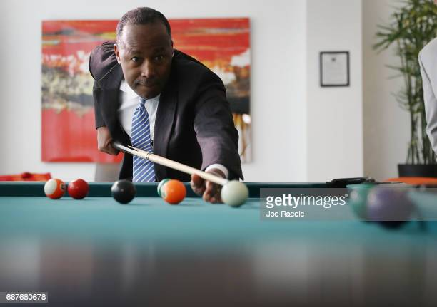 S Housing and Urban Development Secretary Ben Carson lines up a shot on the pool table as he visits Colllins Park apartment complex on April 12 2017...
