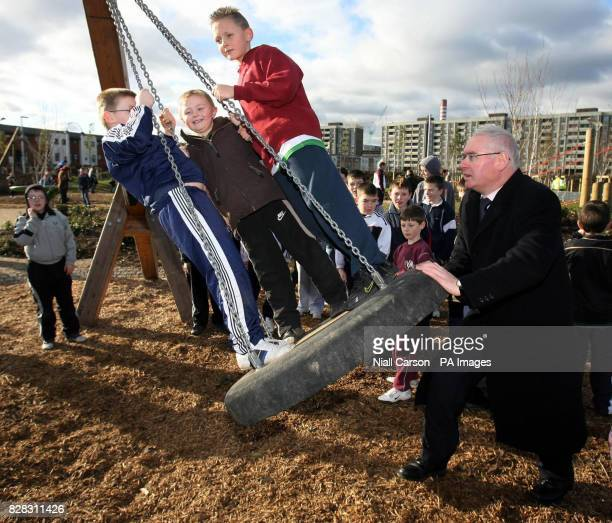 Housing and urban renewal minister Noel Ahern pushes children on a swing in the Coultry Neighbourhood Park Dublin which he opened Saturday January 28...