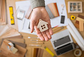 Real estate agent holding a small house, desktop with tools, wood swatches and computer on background, top view