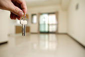 Apartment key in man hand in closeup view as house rental concept